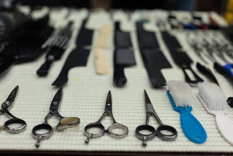 Tabela de trabalho do barbeiro com um grupo de tesouras imagens de stock royalty free