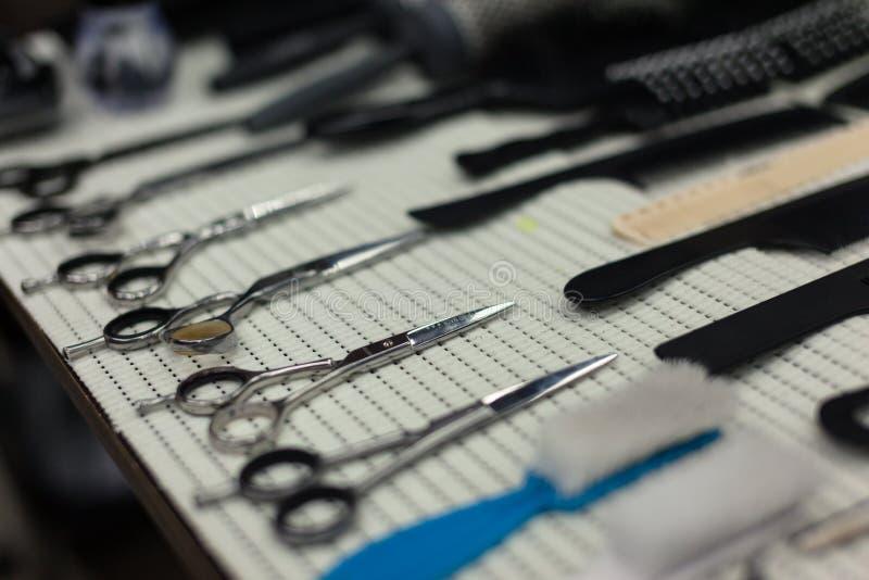 Tabela de trabalho do barbeiro com um grupo de tesouras fotografia de stock