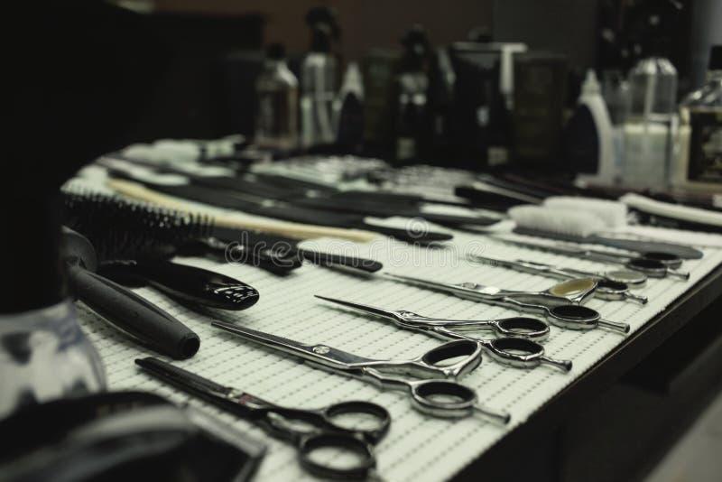 Tabela de trabalho do barbeiro com um grupo de tesouras fotos de stock royalty free