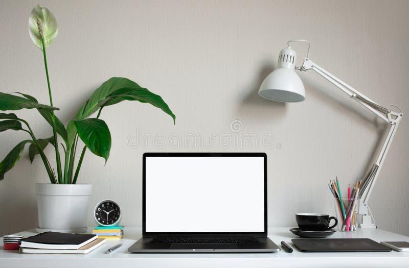 Tabela de trabalho moderna com o portátil e os acessórios vazios do computador no estúdio do escritório domiciliário Ideias autôn imagem de stock