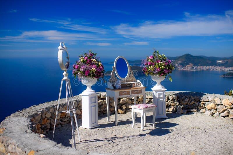 Tabela do boudoir com flores e um espelho fotografia de stock