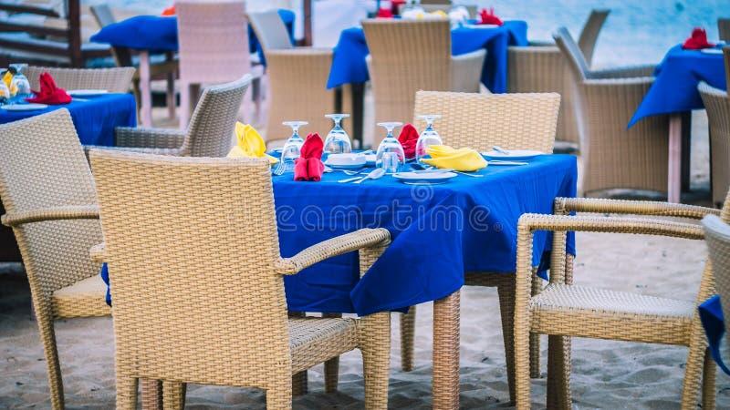 Tabela do café em um Sandy Beach tropical com o mar no fundo, DUA de Nusa, Bali foto de stock
