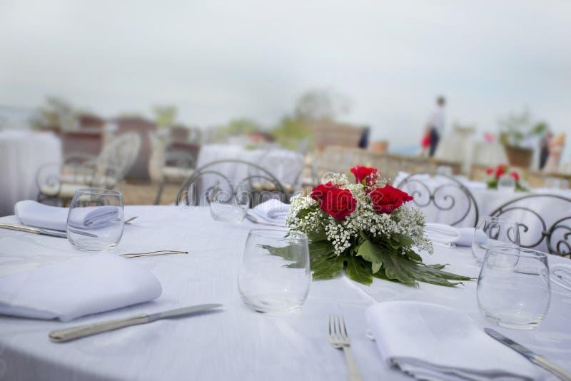A tabela do casamento ajustou-se com as rosas de linho e vermelhas brancas fotos de stock