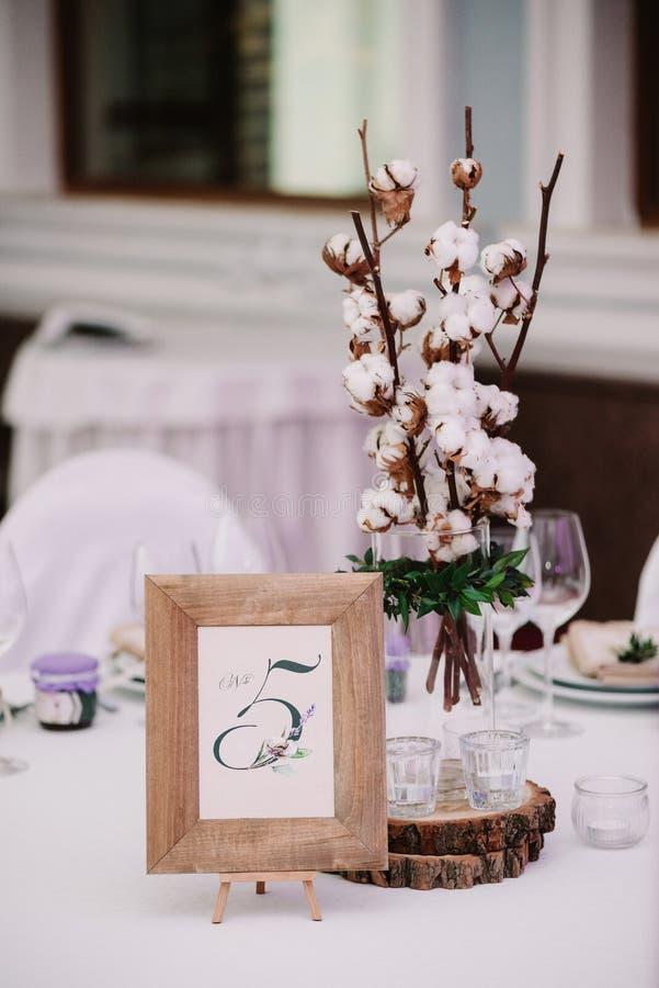 Tabela do convidado, com o ramalhete do algodão e o quadro com número imagens de stock