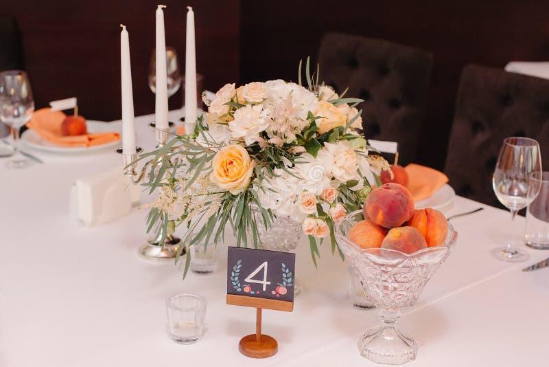 Tabela do convidado do casamento decorada com ramalhete e ajustes imagens de stock royalty free