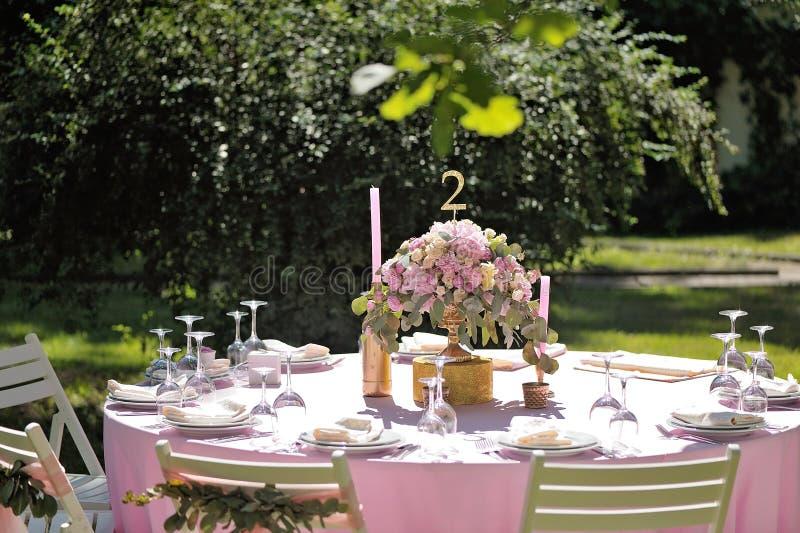 Tabela do convidado do casamento decorada com ramalhete e pano imagens de stock