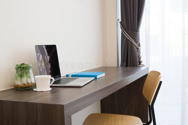 Tabela do escritório com o portátil da tela vazia, copo de café branco, moderno imagens de stock royalty free