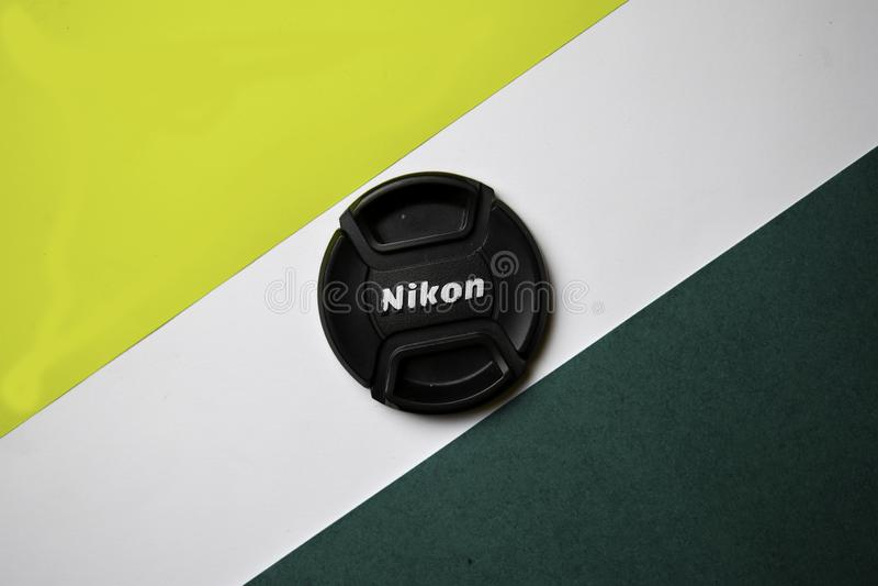 Tabela do escritório com a tampa de lente de Nikon no fundo da cor imagens de stock royalty free
