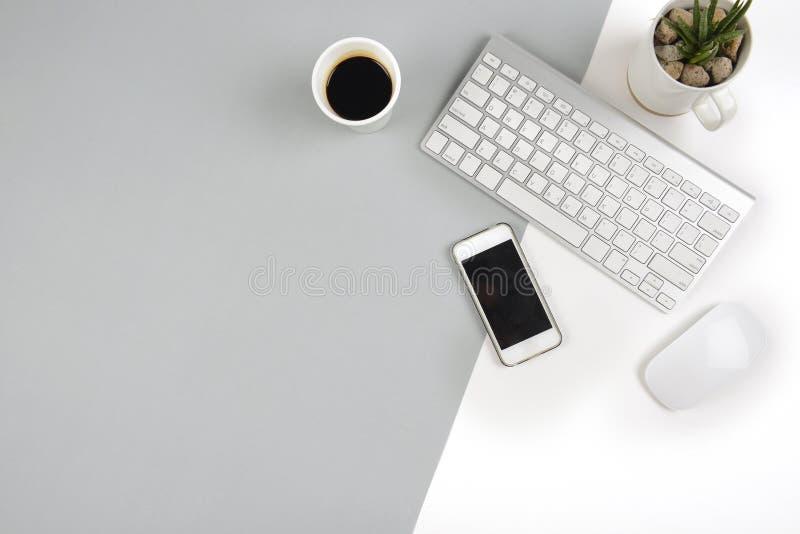 A tabela do escritório com teclado, o rato, e o smartphone em dois modernos tonificam o fundo branco e cinzento imagem de stock royalty free