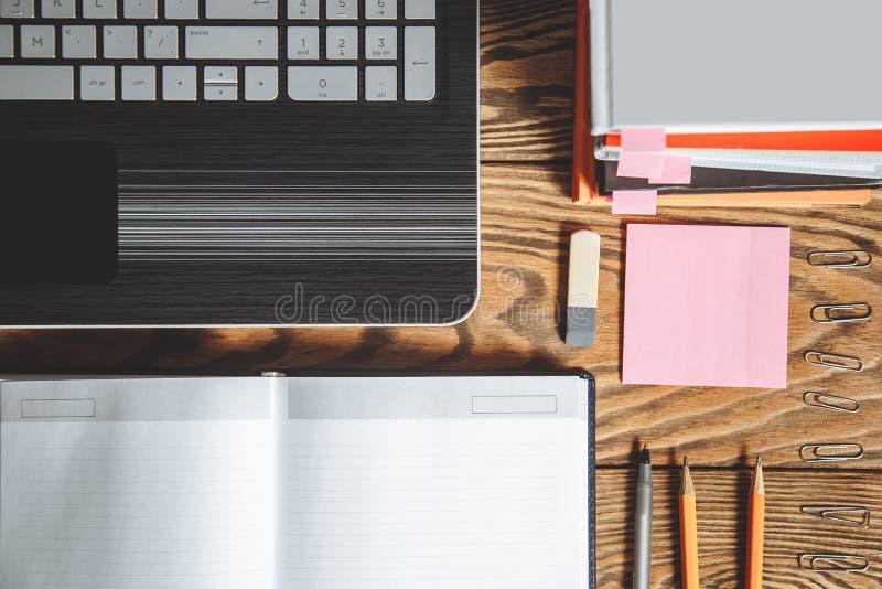 Tabela do escritório da vista superior com os acessórios do espaço de trabalho e do escritório no fundo de madeira imagens de stock