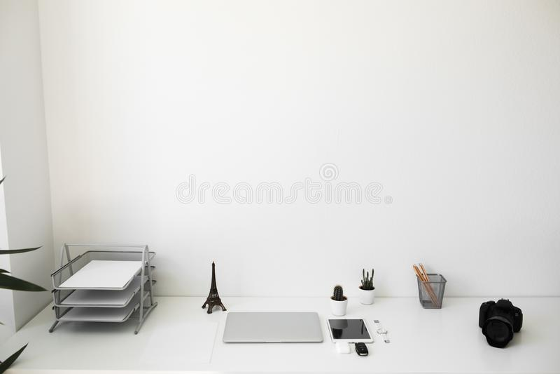 Tabela do escritório em que portátil, em café, em tabuleta, em câmera e em outros artigos fotos de stock royalty free