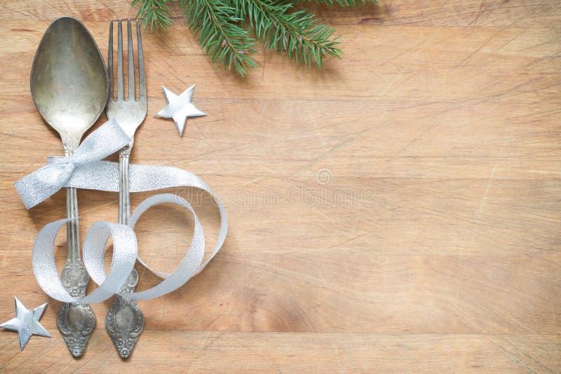 Tabela do Natal com as estrelas do abeto da cutelaria e o ornamento de prata da fita no fundo de madeira foto de stock