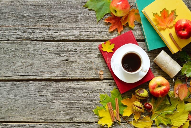 Tabela do outono do vintage com maçãs, as folhas caídas, os livros do vintage, a xícara de café ou o chá na tabela de madeira vel fotografia de stock royalty free