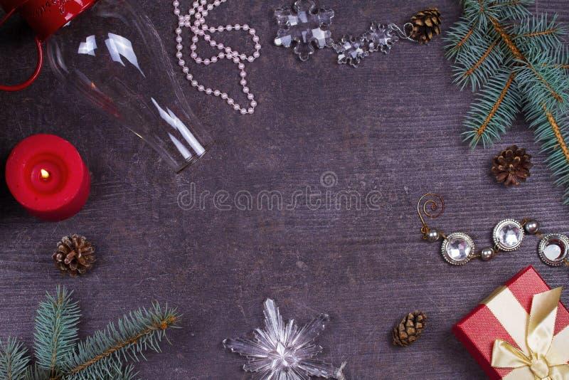 Tabela do serviço do Natal - placa, vidro, lâmpada, vela, cones do pinho, caixa de presente Vista superior Fundo rústico com espa fotografia de stock