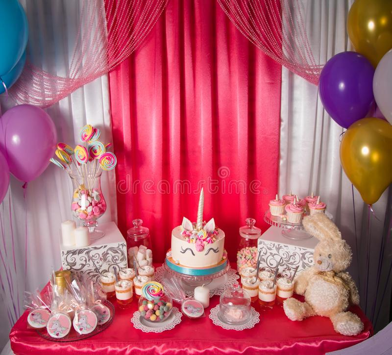 A tabela doce e o unicórnio grande endurecem para o primeiro aniversário do bebê A barra de chocolate com muitos doces e doce dif imagens de stock