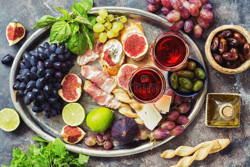 Tabela dos aperitivos com os petiscos e vinho italianos do antipasto nos vidros em uma bandeja do metal Grissini dos palitos com  imagem de stock