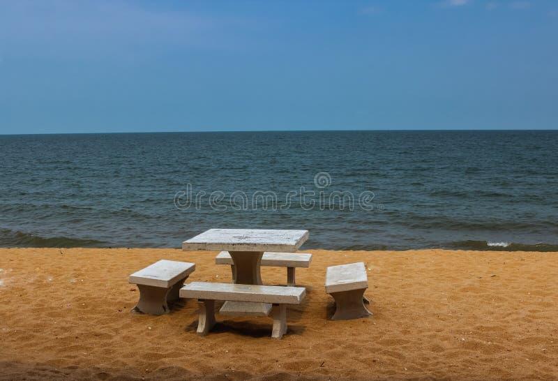 A tabela e as cadeiras de mármore na praia foto de stock royalty free