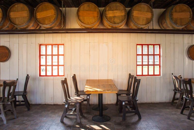 A tabela e as cadeiras de madeira velhas localizam no restaurante com interior de madeira do tambor de vinho no restaurante imagem de stock royalty free