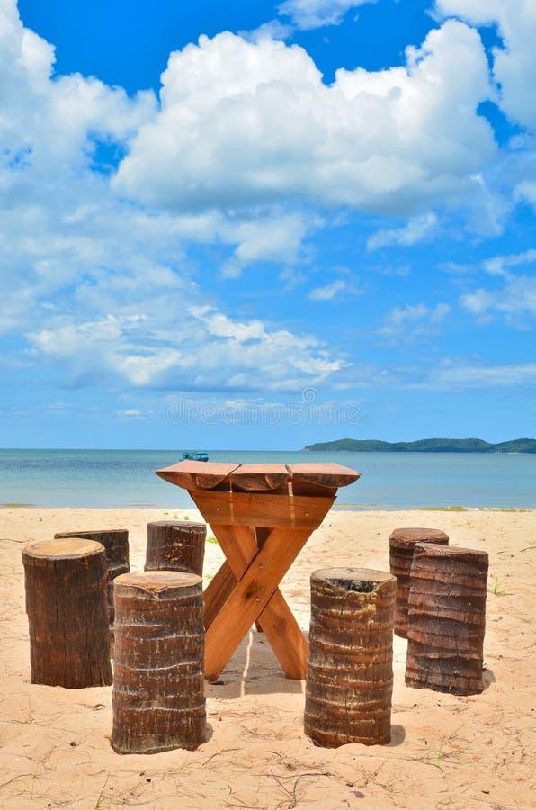 Tabela e cadeira de madeira na praia bonita fotografia de stock royalty free