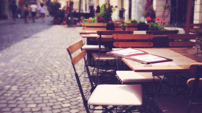 Tabela e cadeira europeias exteriores do café do passeio imagens de stock