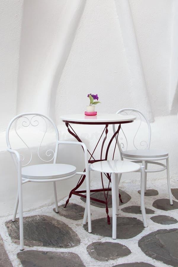 Tabela e cadeiras brancas no café na rua fotografia de stock