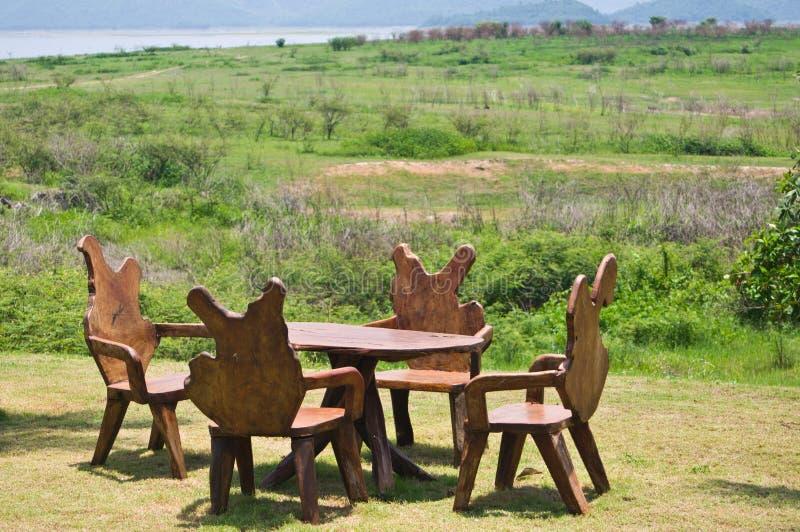 Tabela e cadeiras de madeira na pastagem foto de stock