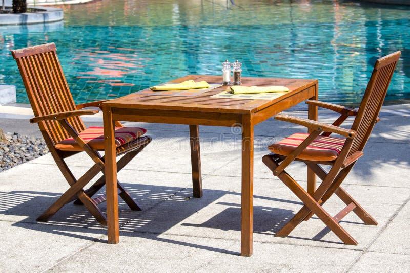 Tabela e cadeiras de madeira no restaurante da praia ao lado da piscina em Tailândia imagem de stock