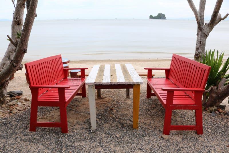 Tabela e cadeiras de madeira vermelhas na praia imagens de stock