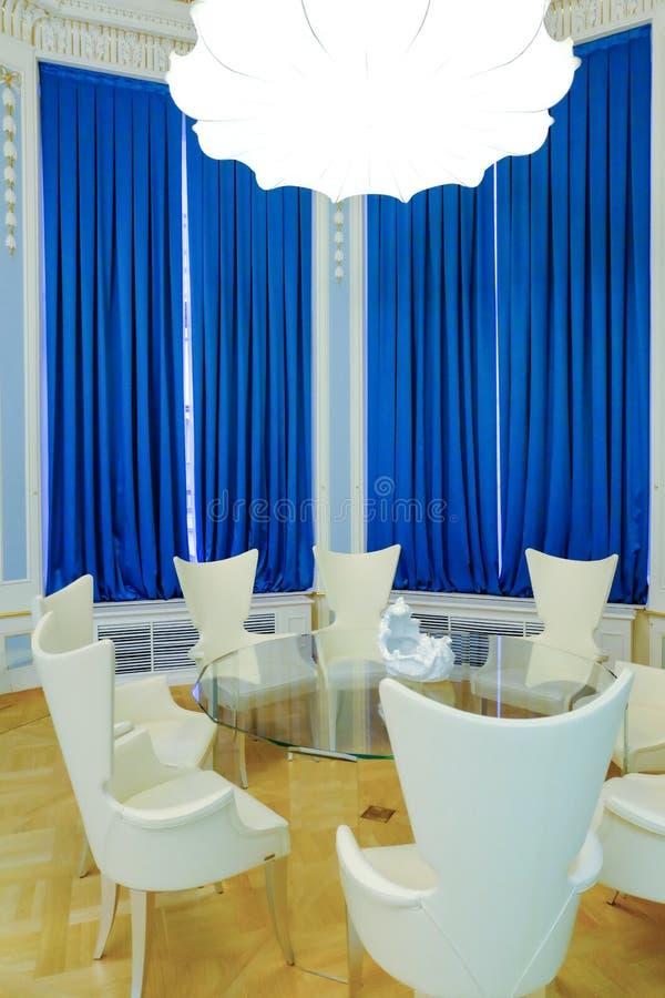 Tabela e cadeiras de vidro contra cortinas azuis Mesa redonda com as cadeiras na sala redonda imagens de stock