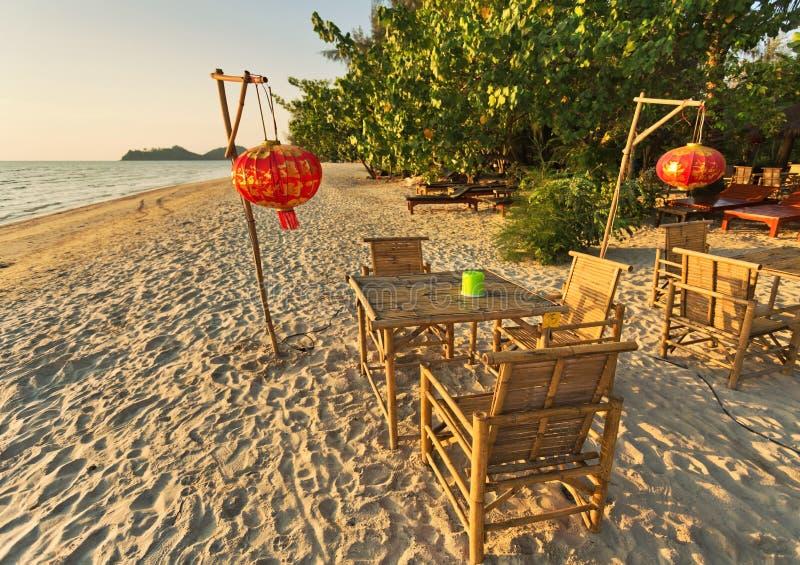 Tabela e cadeiras em uma praia tropical com opini?es do por do sol imagens de stock