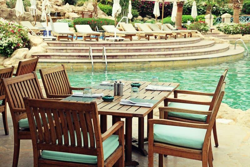 Tabela e cadeiras no café exterior ao lado do poo da natação do recurso imagem de stock