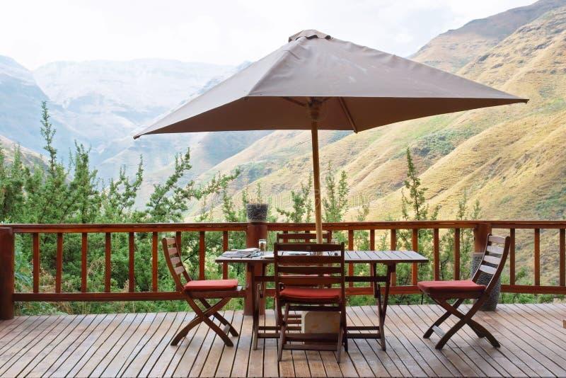 Tabela e cadeiras sob o guarda-chuva no terraço contra a montagem impressionante foto de stock royalty free