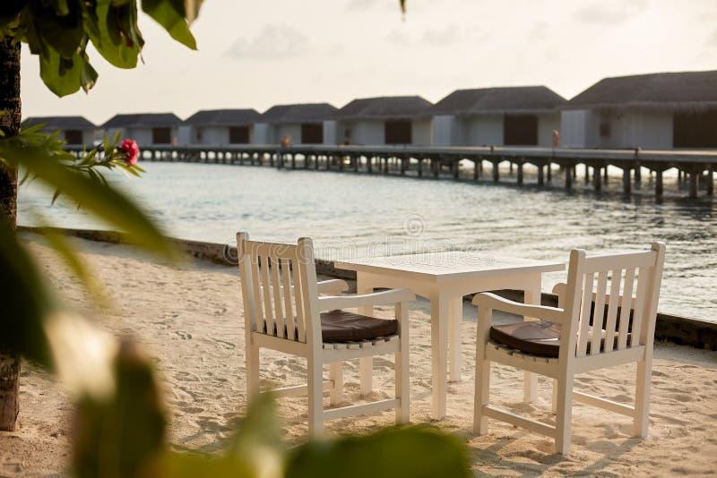 Tabela e cadeiras vazias brancas da tabela no resrraunt tropical na praia em maldives Bungalows azuis da lagoa e da água do ocean imagem de stock