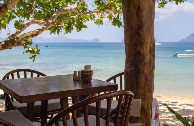 Tabela e cadeiras vazias sob árvores na praia tropical Café da praia no fundo do seascape Mobília exterior da madeira do restaura fotografia de stock