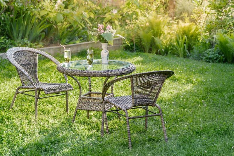 Tabela e duas cadeiras em um jardim fotos de stock