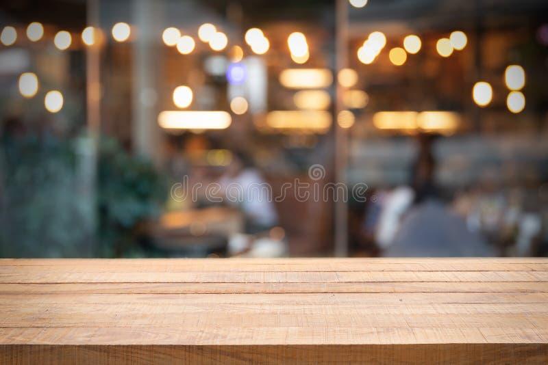 Tabela e foto de madeira vazias do restaurante ou do café borrado imagem de stock royalty free