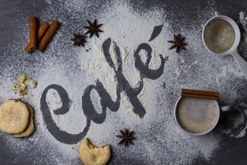 Tabela escura decorada com o café da palavra feito da farinha de trigo fotografada de cima para baixo, mais um grande copo do caf fotografia de stock royalty free