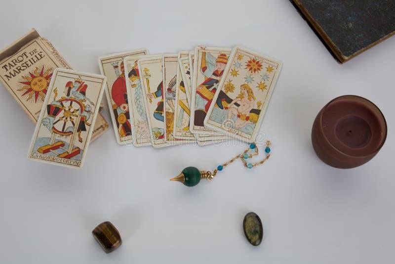 Tabela esotérico com roda astrológica, pêndulo mágico, tarots, pedras curas imagens de stock