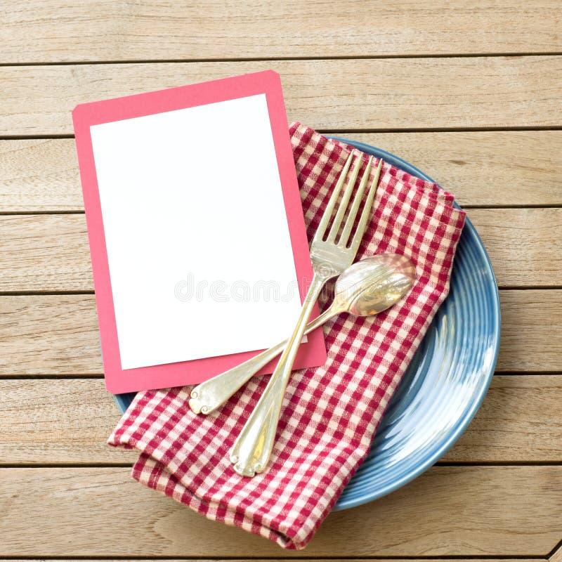 Tabela exterior Placesetting do piquenique do verão com cores brancas e azuis vermelhas com forquilha e colher com um cartão vazi imagem de stock