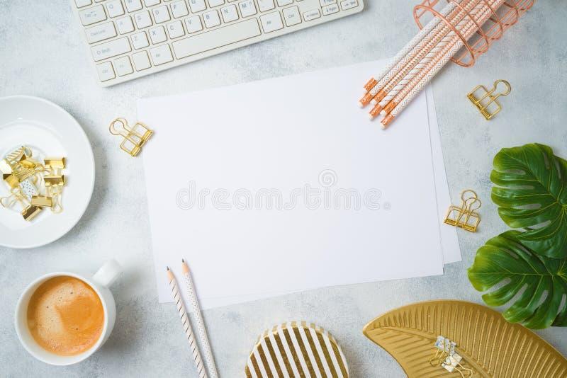 Tabela feminino colocada lisa do escritório domiciliário com papel, os acessórios dourados, o teclado de computador e as folhas t imagens de stock royalty free