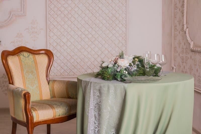 Tabela festiva acolhedor com velas, copos de vinho e placas Jantar romântico Cadeira do vintage Ajuste elegante da tabela Natal fotografia de stock royalty free