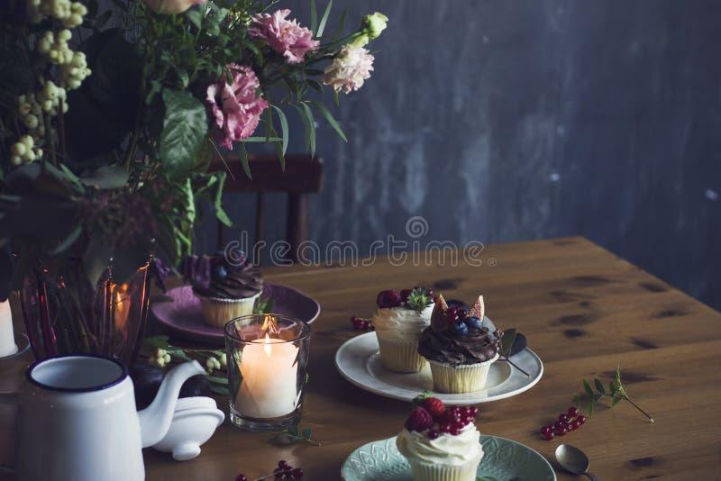 A tabela festiva bonita com ramalhete, os queques e Ca rústicos foto de stock