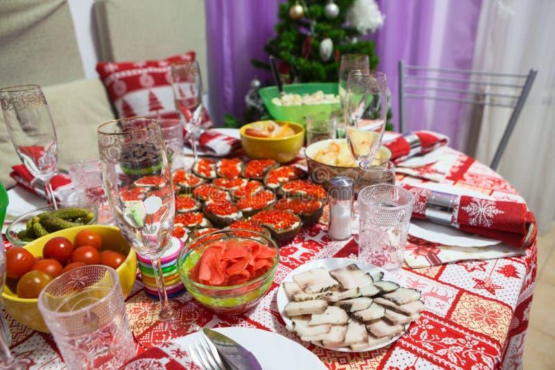 A tabela festiva com o alimento servido com toalha de mesa vermelha do ornamento está pronta para celebrações do Natal ou do ano  fotografia de stock