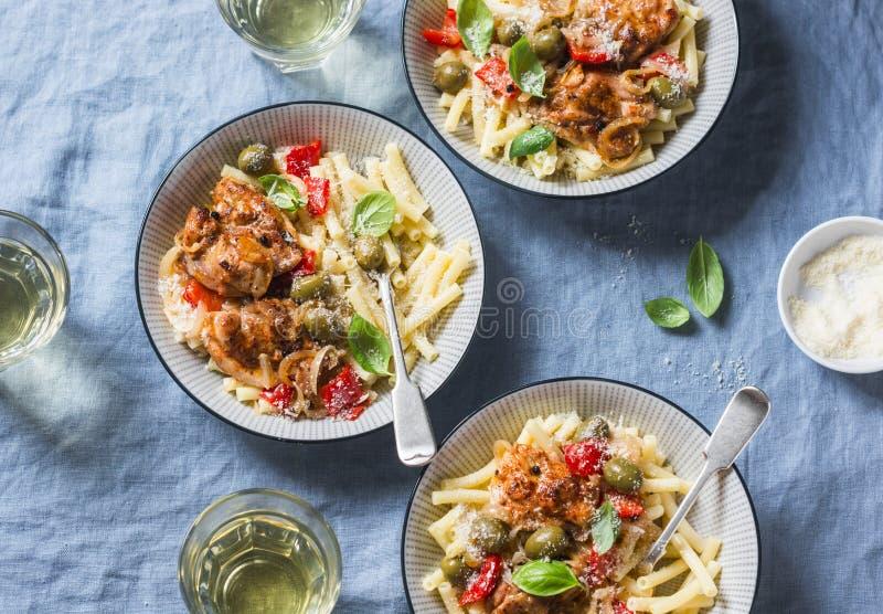 Tabela italiana do alimento Massa com a galinha lenta do fogão com azeitonas e pimentas doces, vinho branco Em um fundo azul fotos de stock royalty free