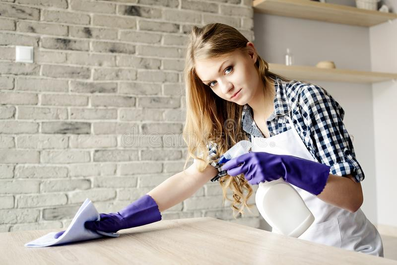 Tabela loura de cabelos compridos de sorriso da limpeza da mulher em casa fotografia de stock
