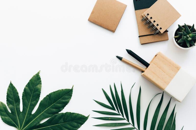 Tabela mínima da mesa de escritório com grupo, fontes e folhas de palmeira dos artigos de papelaria fotografia de stock royalty free