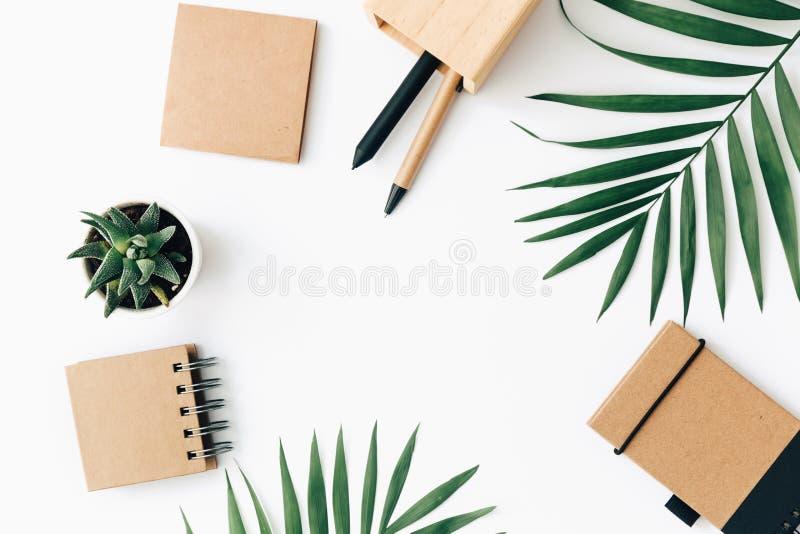 Tabela mínima da mesa de escritório com grupo, fontes e folhas de palmeira dos artigos de papelaria fotografia de stock