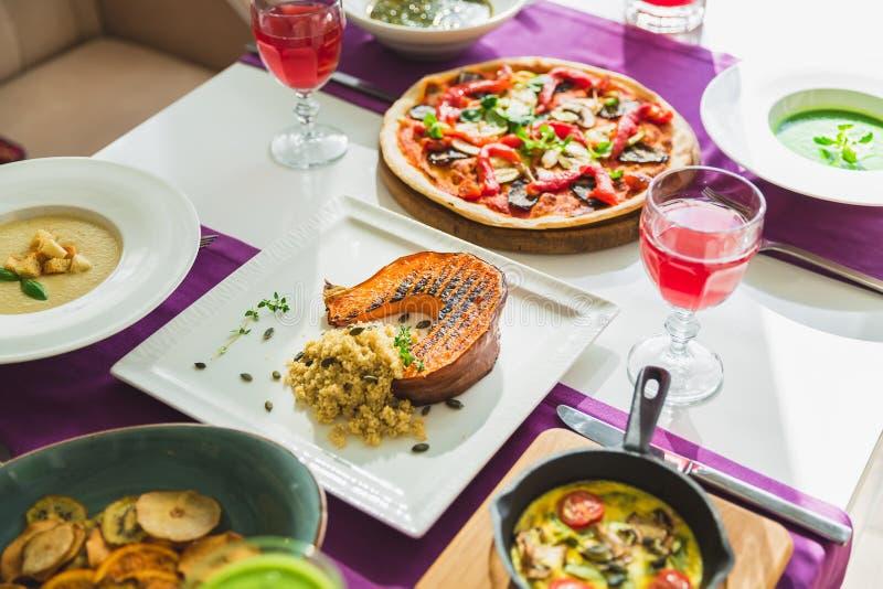 Tabela no café com pratos de vegetariano - pizza, saladas, abóbora e sucos de fruta frescos imagem de stock royalty free
