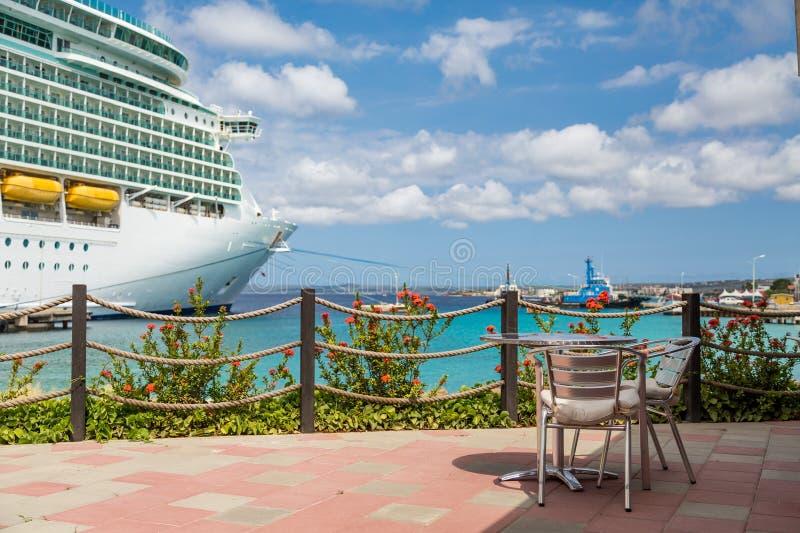 Tabela no pátio do restaurante com o navio de cruzeiros no fundo fotos de stock royalty free