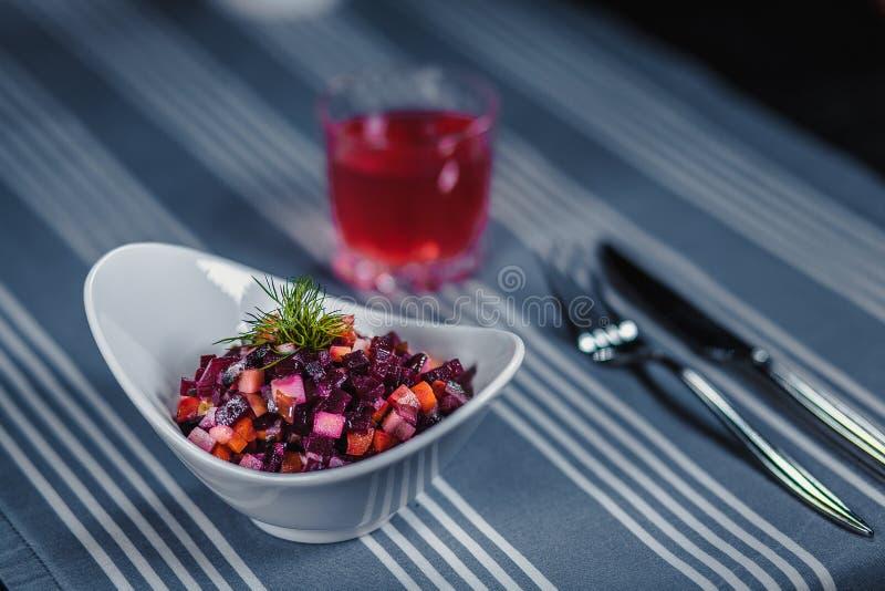 Tabela no restaurante Na tabela é uma salada em uma placa branca, uma faca, uma forquilha, um vidro com suco vermelho Na tabela imagens de stock royalty free